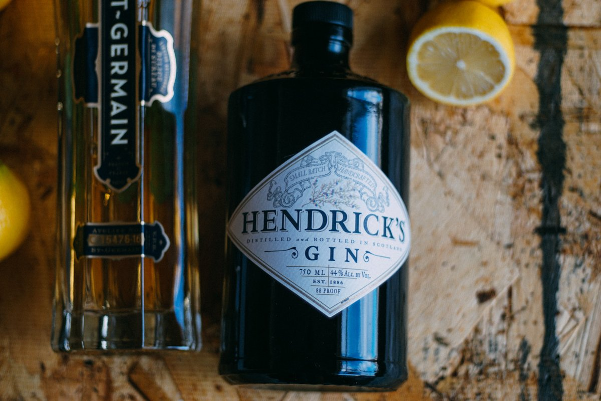 Hendrick's Gin bottle and St. Germain Liqueur bottle on a table.